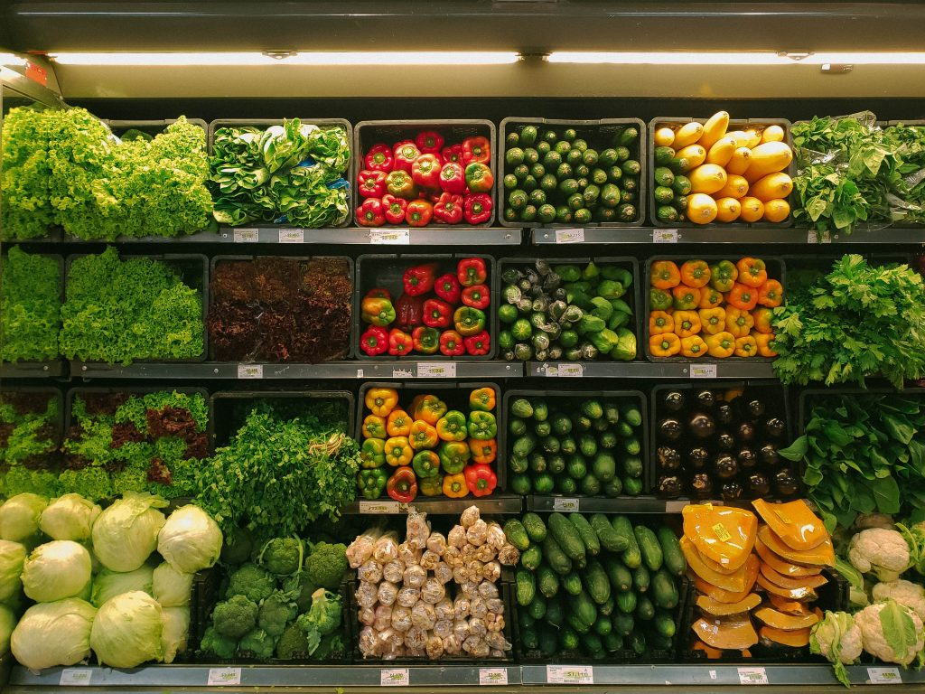 produce aisle in a grocery store filled with vegetables and fruits and other healthy foods