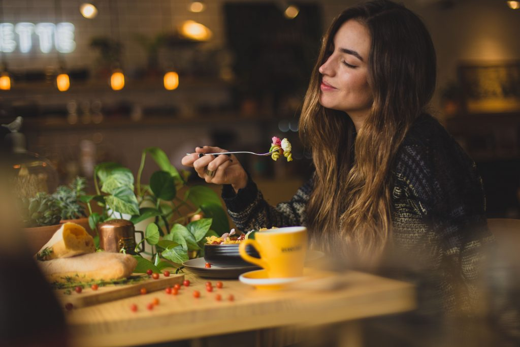 female student sitting down eating healthy food at a restaurant near purdue while smiling