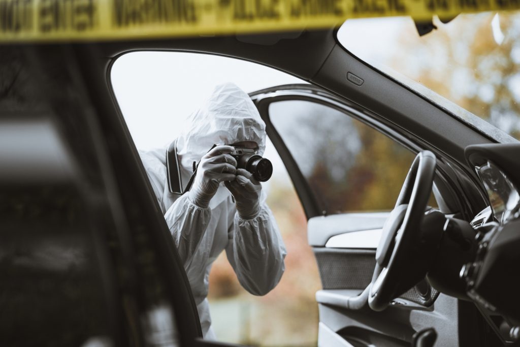 forensic scientist photographing crime scene in a car