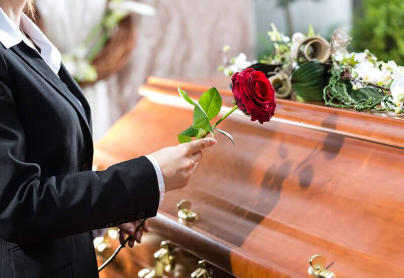 picture of person placing rose upon casket during funeral