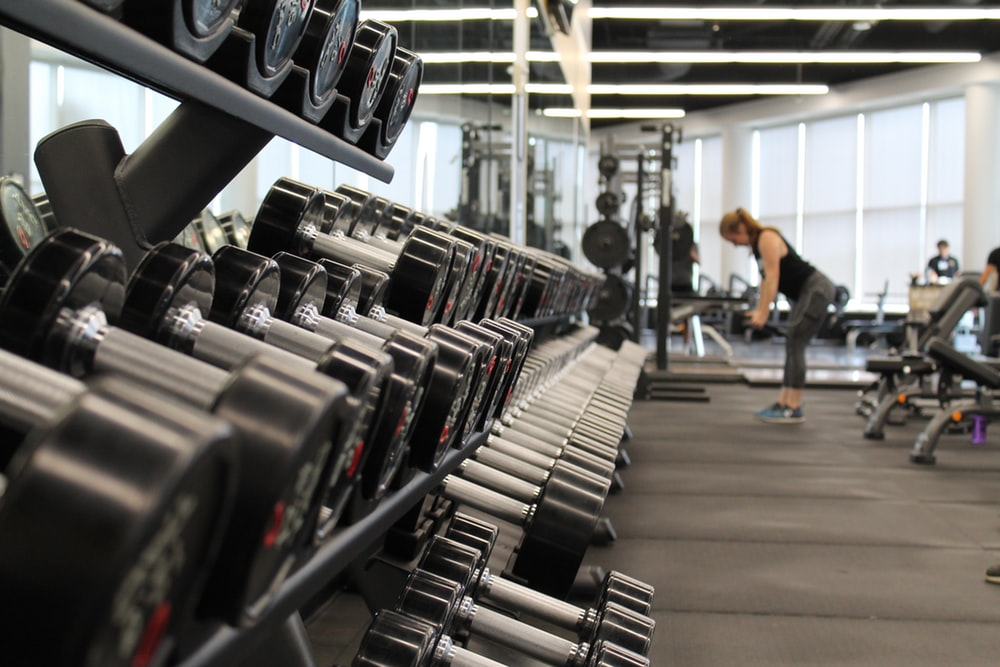 female student working out in campus gym with lots of weights around her