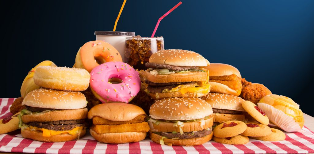 pile of burgers, donuts, milkshakes, fried chicken, etc. on a table