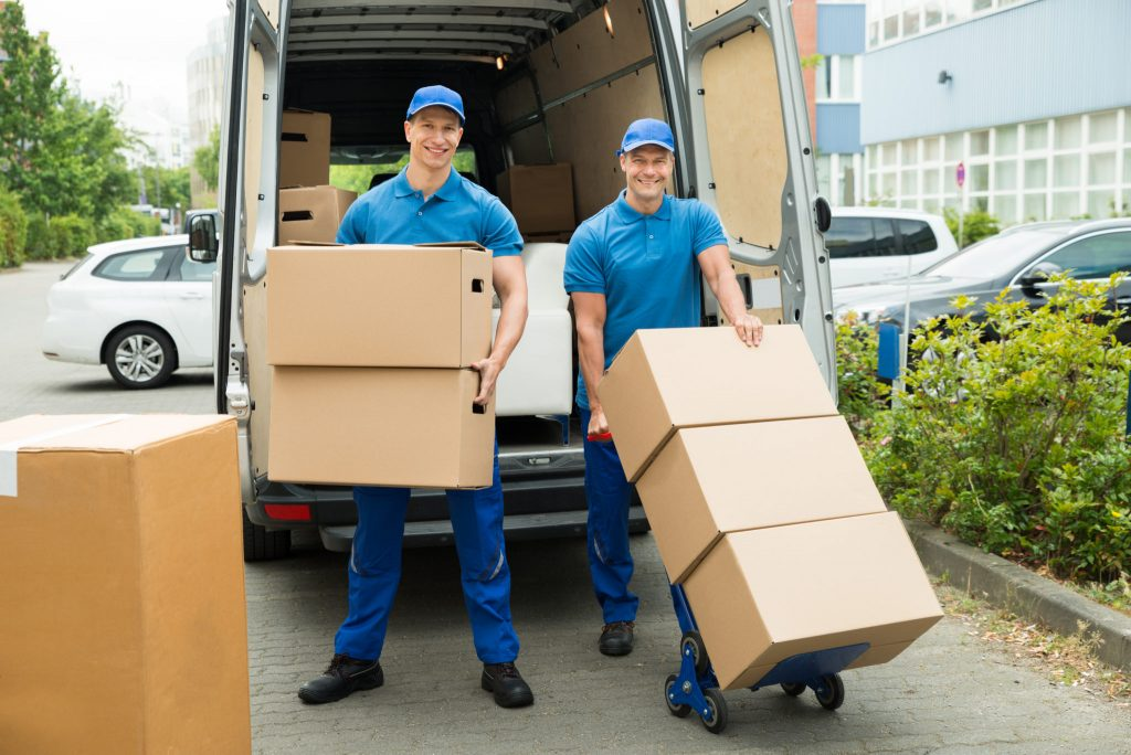 Two Happy Male students Loading Stack Of Cardboard Boxes Into a moving Truck rental