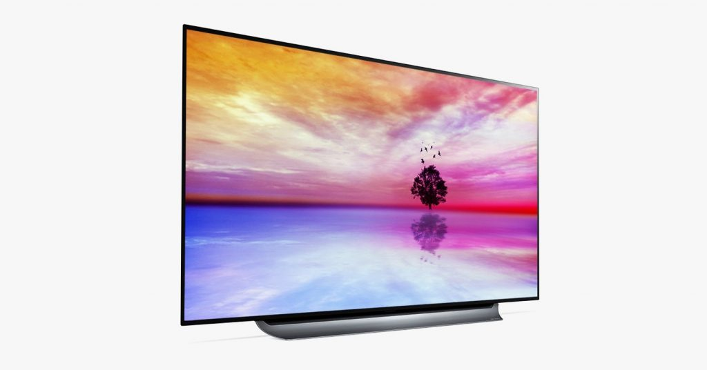 A flatscreen TV with an image of warm colored sky and a silhouette of a tree in the background.