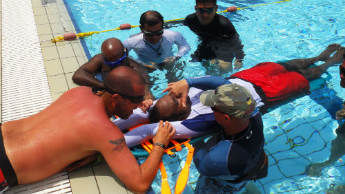 A first Aid team attending to a person in a swimming pool