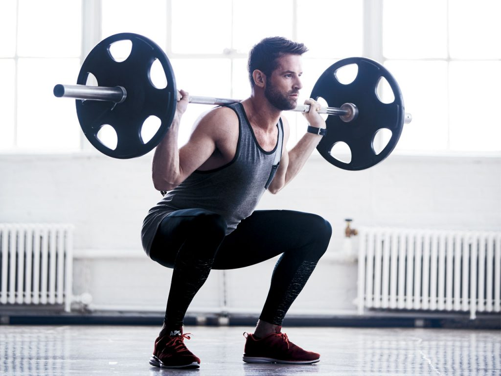 A man squatting with weights over his shoulder