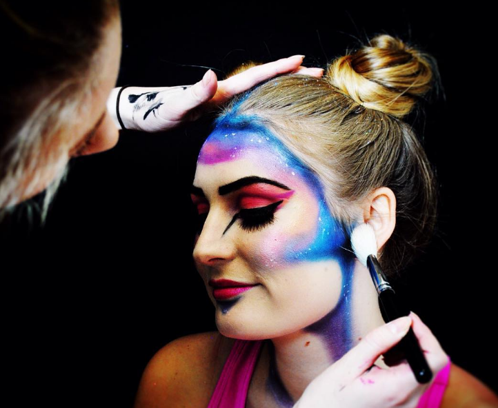 A female performer being applied make-up on her face