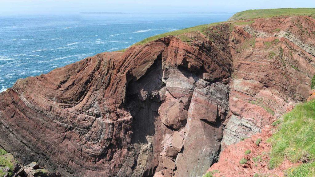 A rocky cliffside overselling an ocean below.
