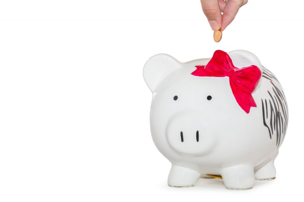 person inserting a coin into a piggy bank to save money as a college student