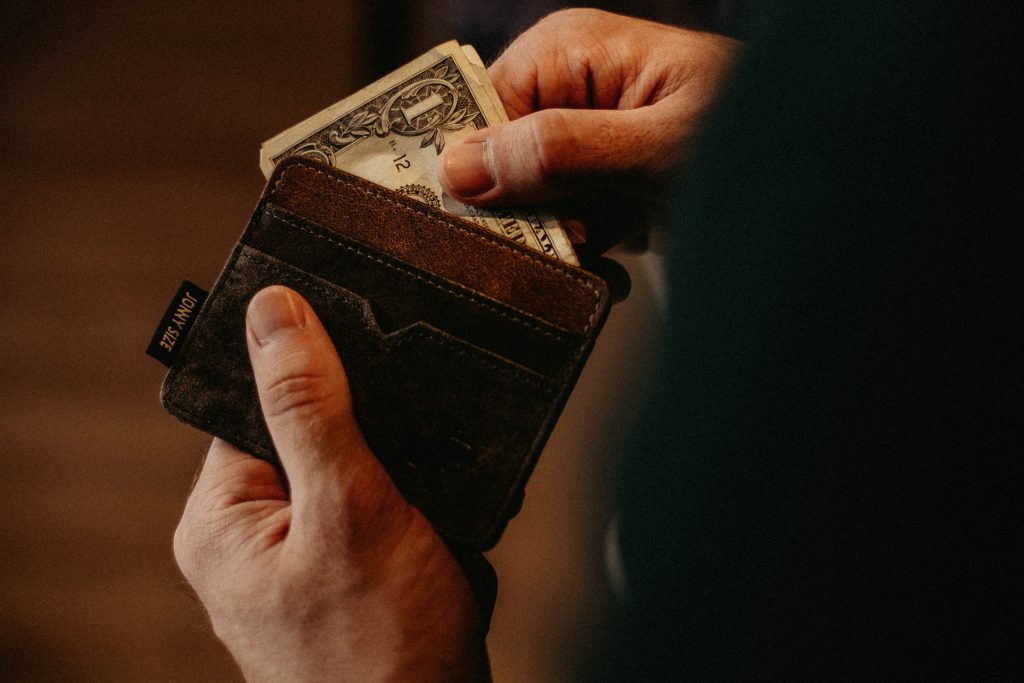 male student taking US dollar bills out of his wallet