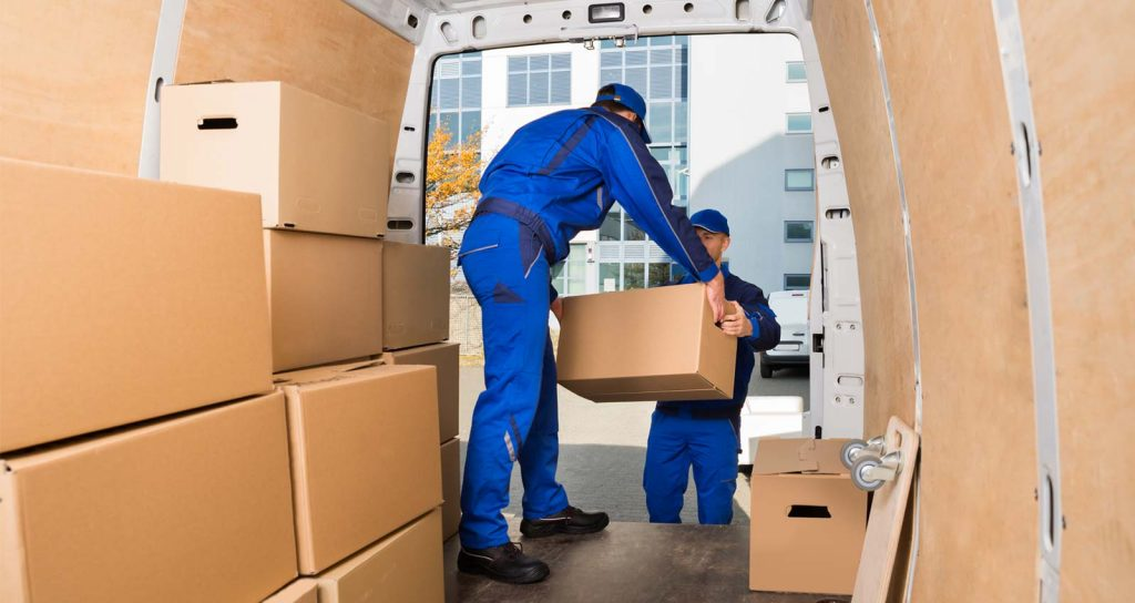 movers in blue uniforms moving boxes out of a moving truck