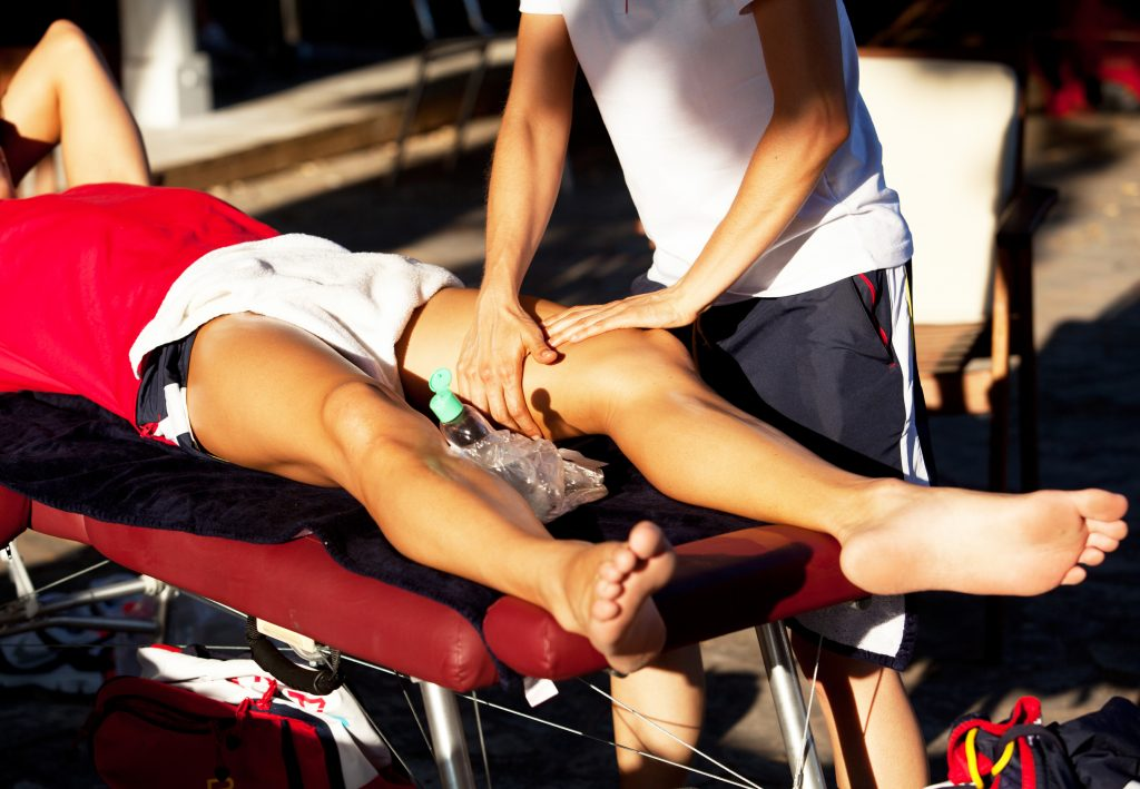 A first aider attending to an athlete's injury