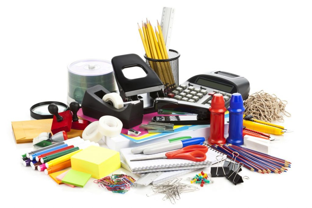 A pile of office or school supplies such as markers, tape, pens and pencils, paper, calculators, etc.