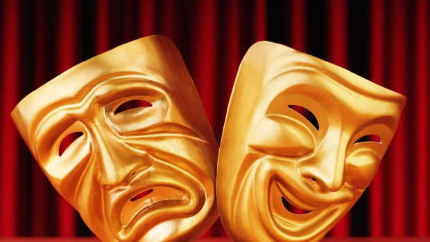 Two golden acting masks in front of a maroon curtain