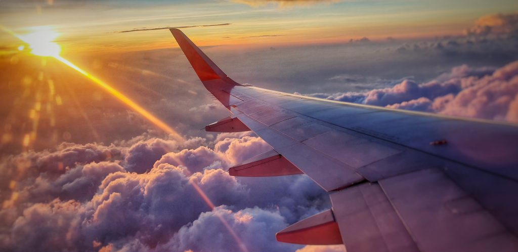 view of an airplane wing from a window seat high above the clouds with the sun setting