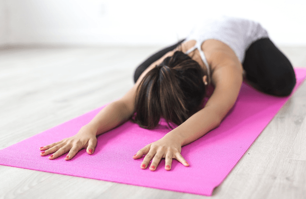 woman performing yoga on a yoga mat