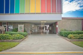 Front view of the building with a rainbow wall in the upper location of the building.