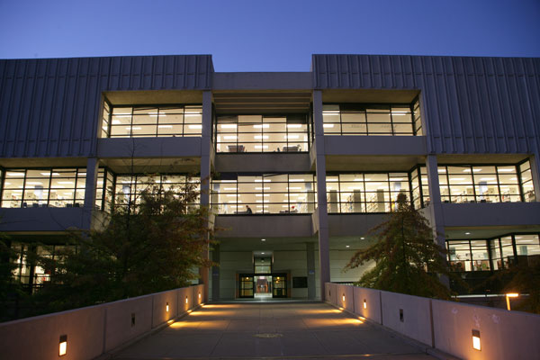 Front view of the library during the evening time with lights lighting the sidewalk.
