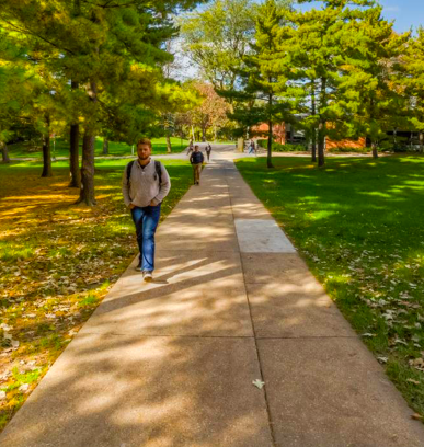 Student walking down a sidewalk toward Quad Creek Café.