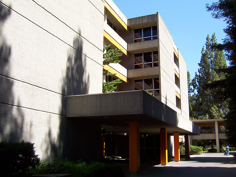 A side view of the hall with shadows of trees represented on the walls during the daytime.