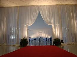 Interior of Elliott Hall all decorated in white drapes and round tables.