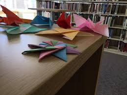 a table with paper cranes in a library