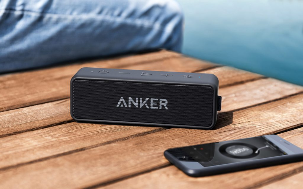 anker speaker next to an iphone playing music on a dock in the summer