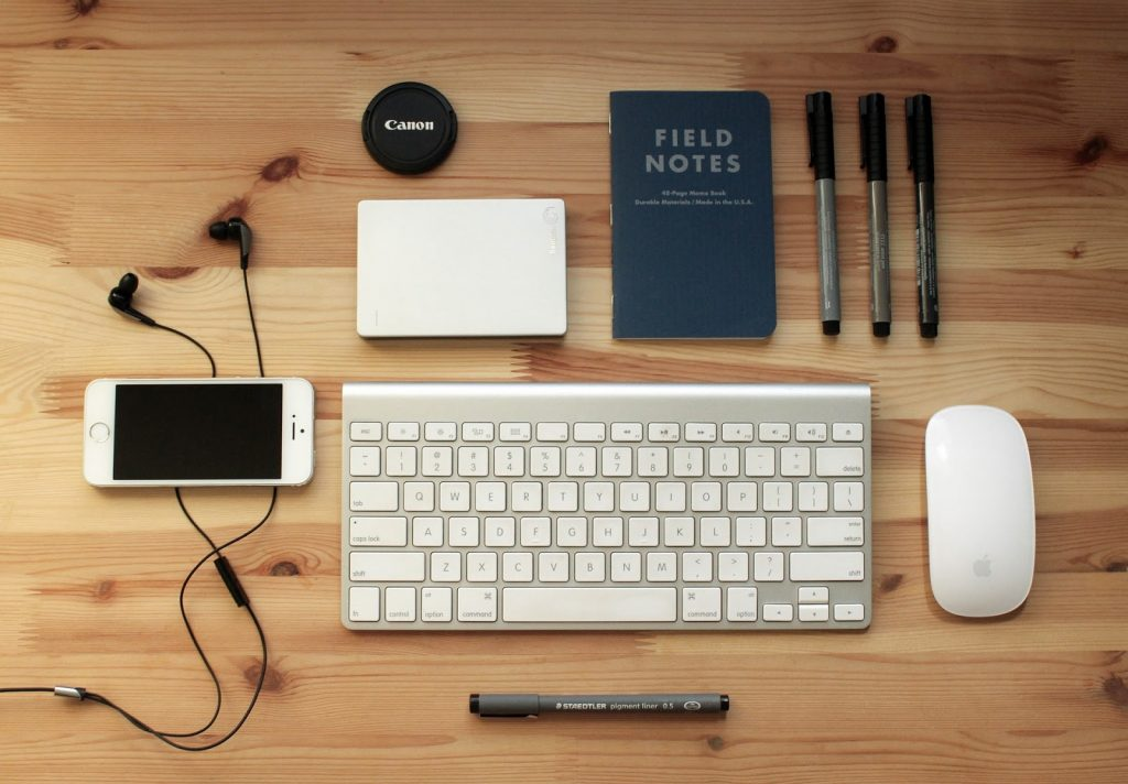 technology products laid out on a table such as an apple keyboard, apple mouse, iphone, earphones, etc.