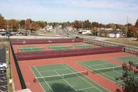 Multiple tennis courts next to a parking lot.