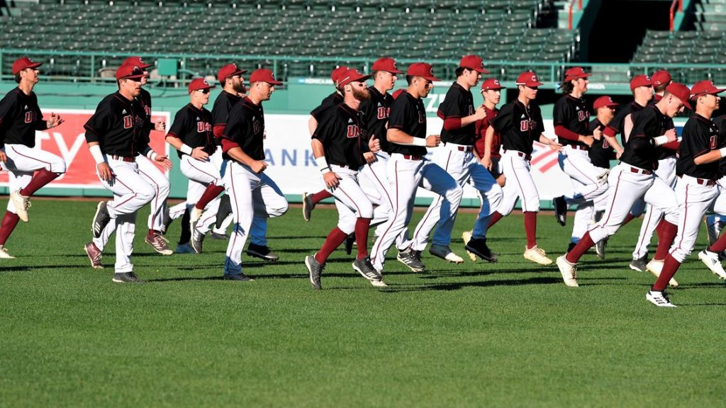 The UMass baseball team jogging on the pitch