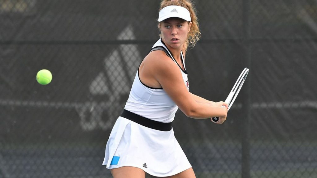 A female tennis player positioned to receive the ball