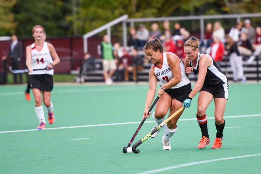 Female  field hockey players contesting on the pitch