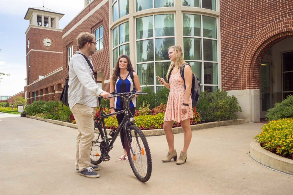 three students walking in front of the pickler memorial library