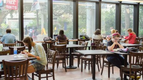 Inside view of the library with students studying at tables.
