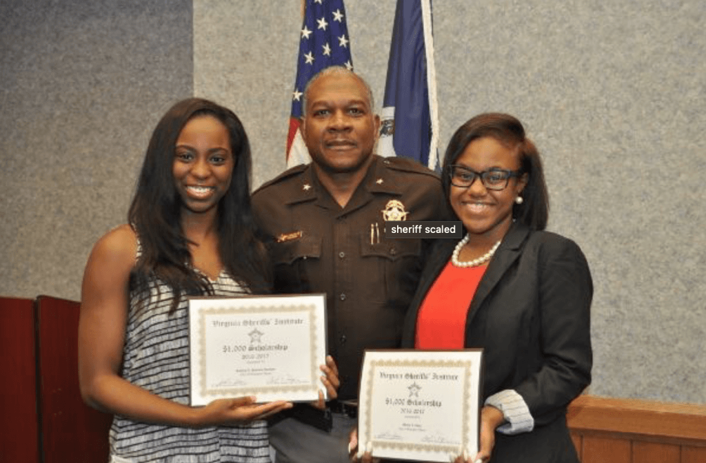 two students with scholarship certificate along with the sheriff