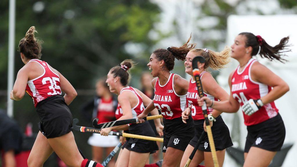 The IU field hockey team running onto the field