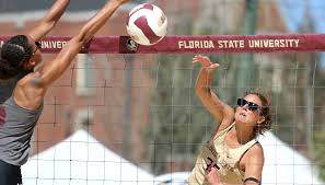 a person grabbing at the volleyball on the beach