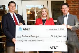 men holding a check for at&t program