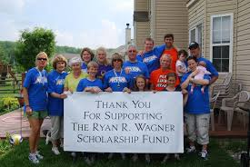 people around a sign raising funds for the ryan r wagner scholarship fund
