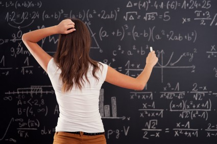Student trying to solve a math problem on the board.