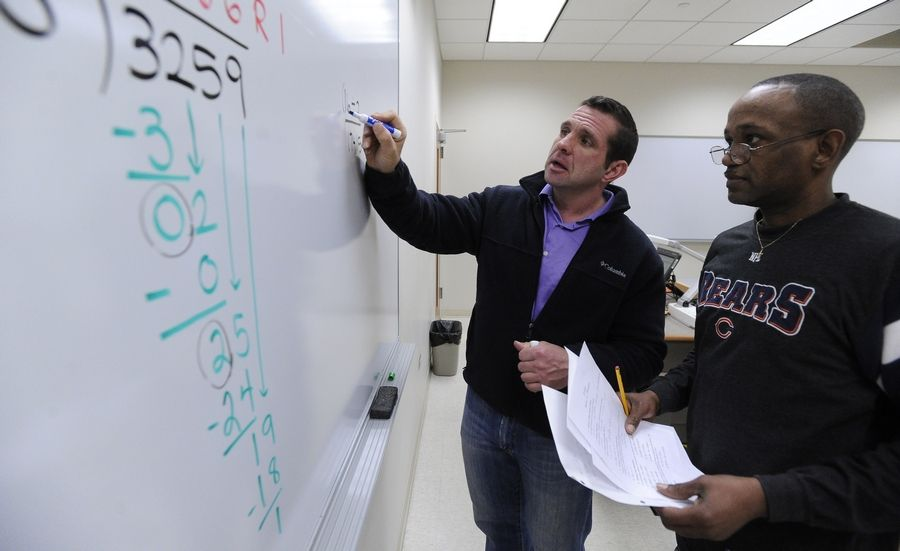 Professor working with student on the whiteboard.