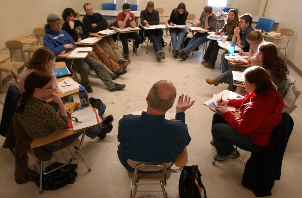 Professor sits in a group with students.
