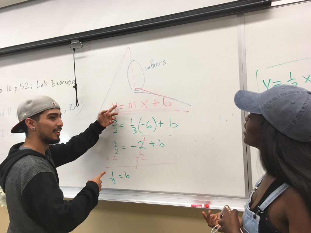 Student working on an equation on the whiteboard.
