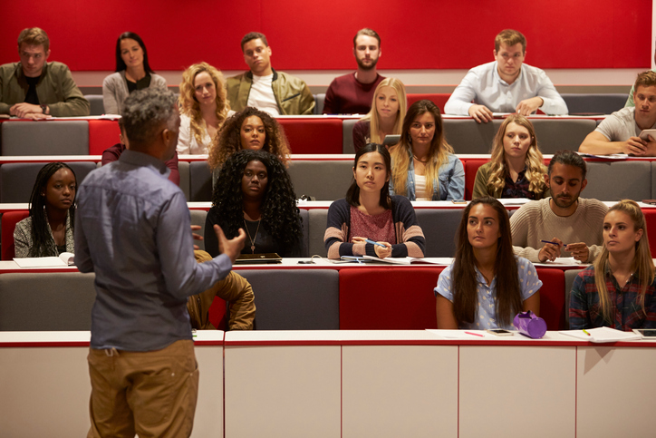 Professor teaching to a  lecture hall of students.
