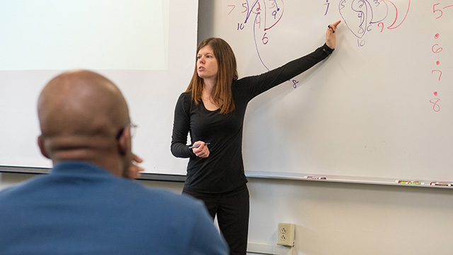 Professor teaching to a group of students.