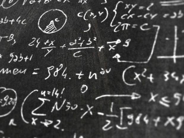 Image of equations on a chalkboard.