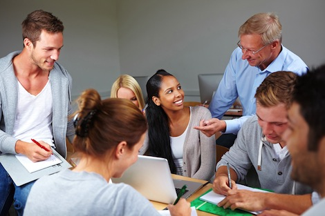 Professor working with a group of students in class.