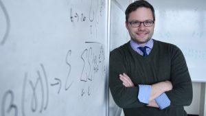 An Adelphi professor leaning on a whiteboard