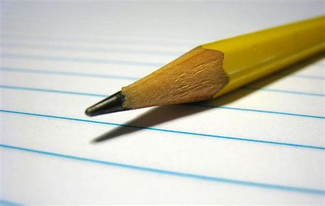 A pencil laying on top of lined paper.