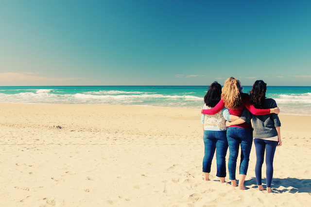a group of friends watching the shoreline at the beach